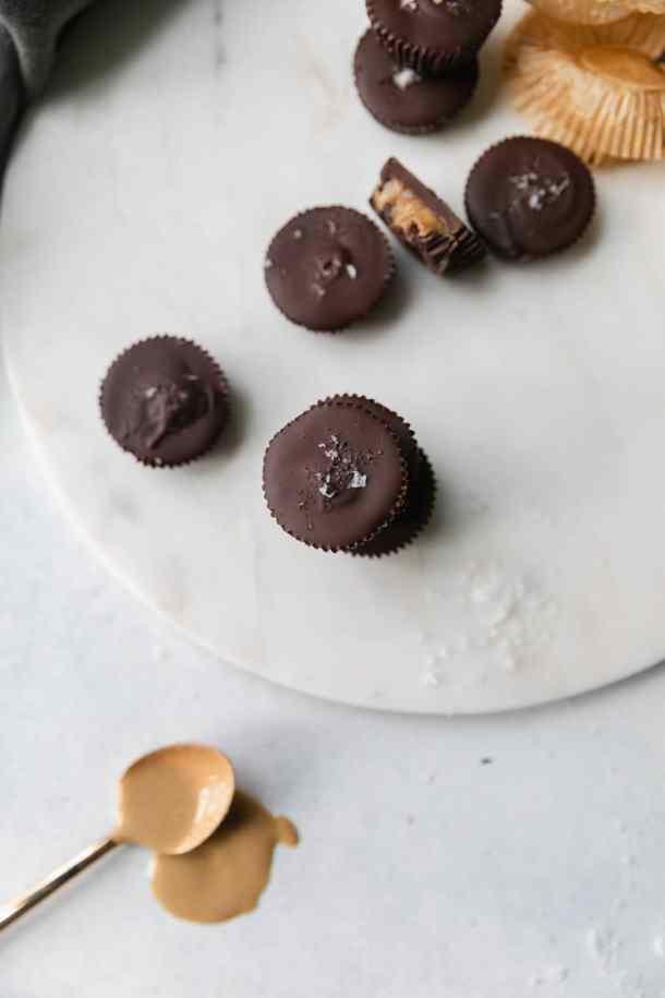 Overhead shot of mini dark chocolate tahini cups with a spoonful of tahini below them