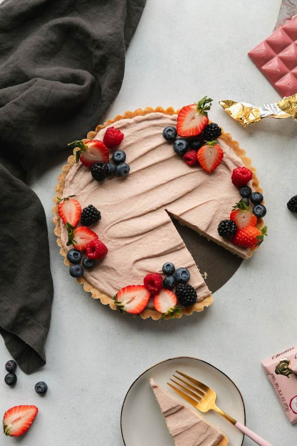 Overhead shot of a berry cheesecake tart with a slice taken out