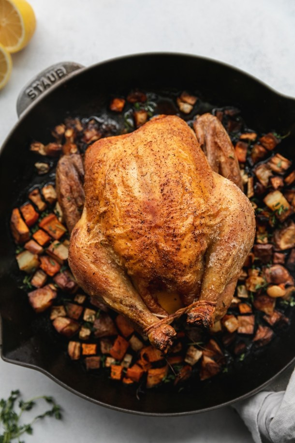 Overhead shot of a whole roasted chicken in a cast iron skillet with root vegetables