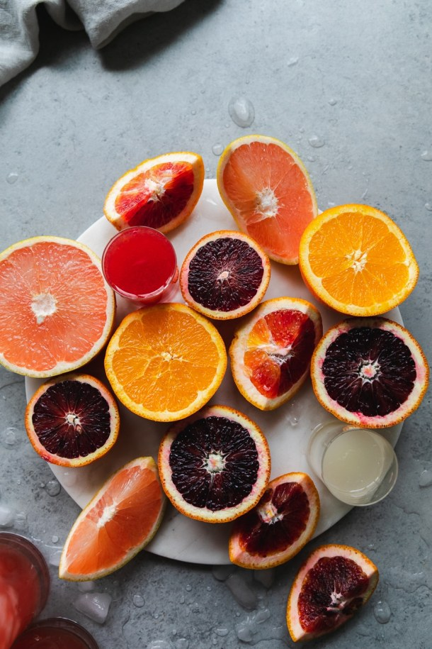 Overhead shot of a bunch of very colorful cut citrus fruits on a circular marble tray