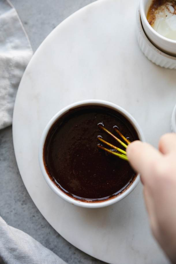 Overhead shot of a bowl of raw chocolate sauce being whisked with a mini green whisk