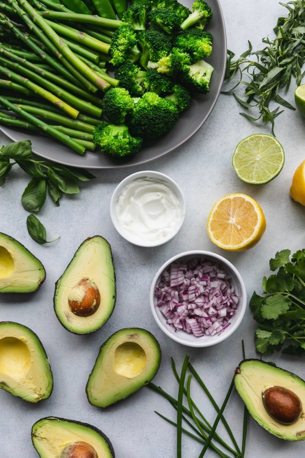 Overhead shot of halved avocados, a bowl of red onion, greek yogurt, a halved lemon, a halved lime, a bundle of cilantro, a sprig of tarragon, and a plate of green vegetables