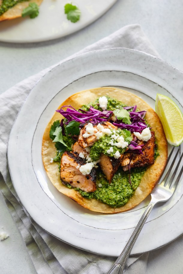 Overhead close up shot of a blackened salmon tostada with green sauce, red cabbage, queso fresco, cilantro, and a lime wedge on a white plate with a silver fork