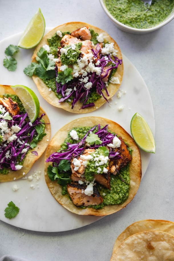 Overhead shot of 3 blackened salmon tostadas with green sauce, red cabbage, queso fresco, cilantro, and a lime wedge