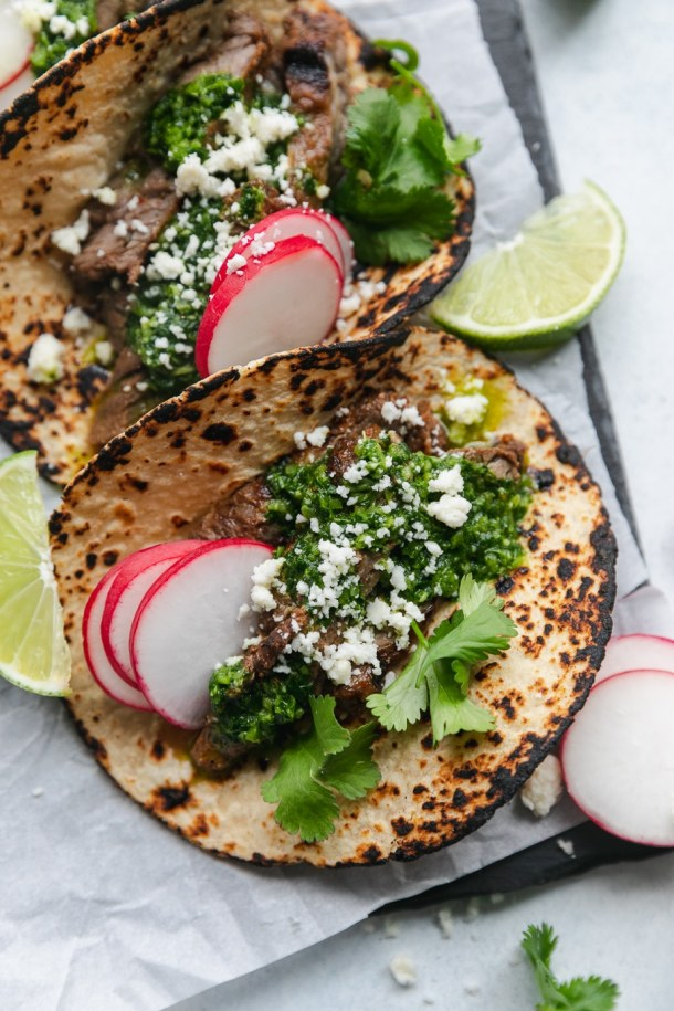 Overhead close up shot of charred tortillas filled with grilled carne asada, chimichurri sauce, cilantro, sliced radishes, cotija cheese, and lime wedges