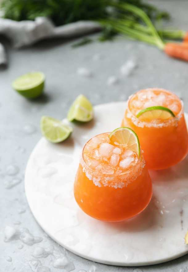 Shot of 2 carrot ginger margaritas on a circular marble board with lime wedges in the background and crushed, melted ice scattered around