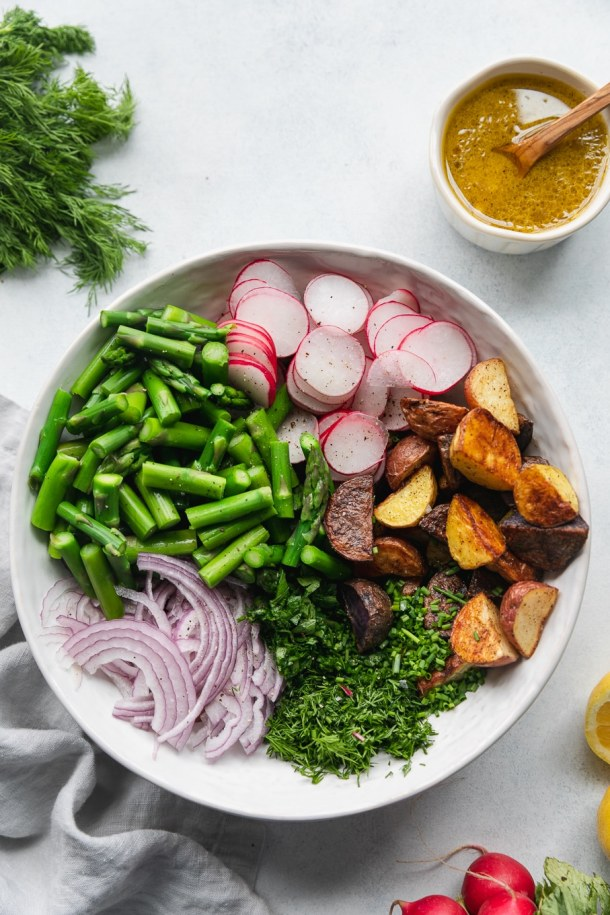 Overhead shot of a white bowl filled with a pile of asparagus, a pile of thinly sliced radish, roasted potatoes, herbs, and red onion