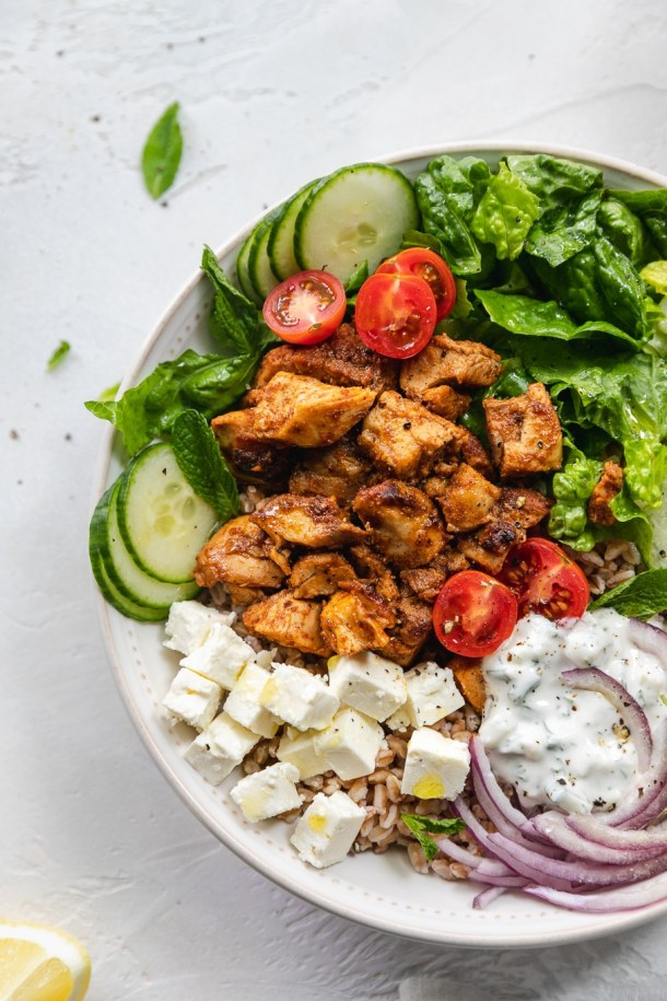 Overhead close up shot of half of a chicken shawarma bowl with cherry tomatoes, red onion, feta, cucumbers, romaine, mint, and tzatziki