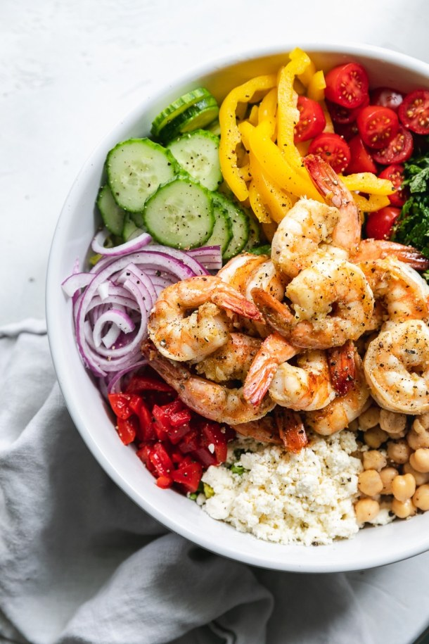 Overhead shot of a mixing bowl filled with mediterranean chopped salad ingredients with shrimp on top