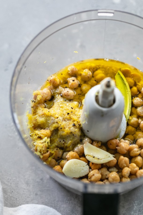 Overhead shot of a food processor filled with chickpeas, garlic, lemon zest, and olive oil