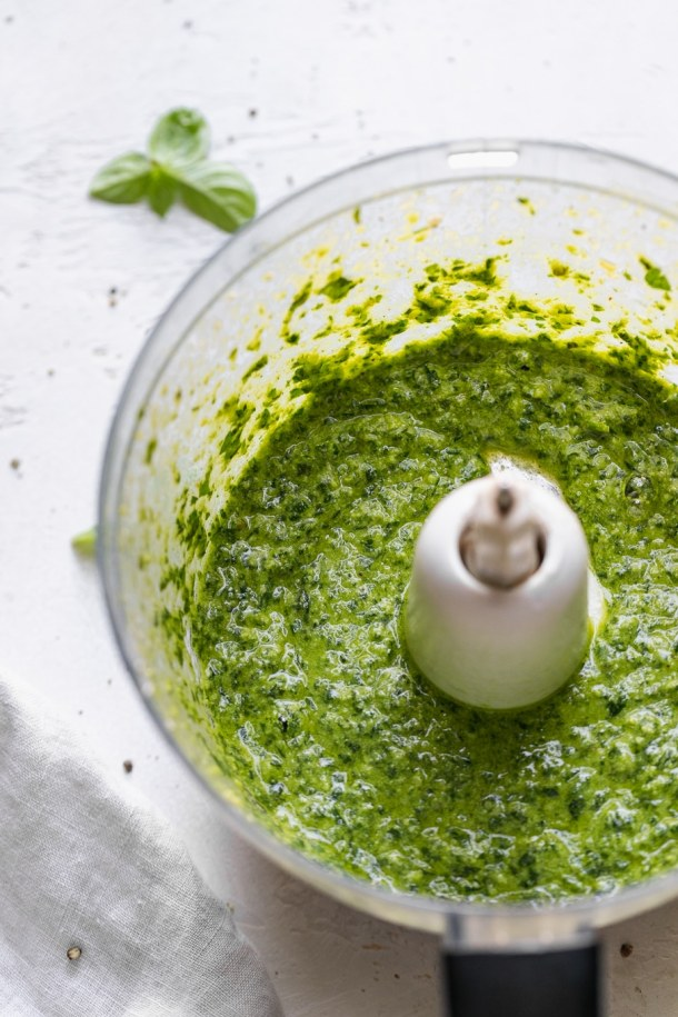 Close up shot of a food processor filled with basil pesto