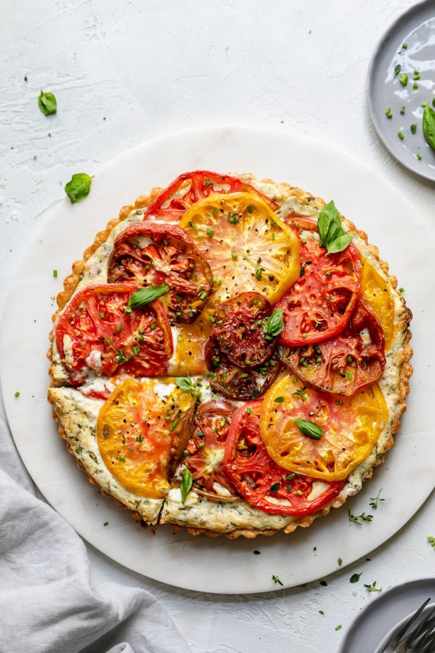 Overhead shot of an heirloom tomato tart with a slice cut