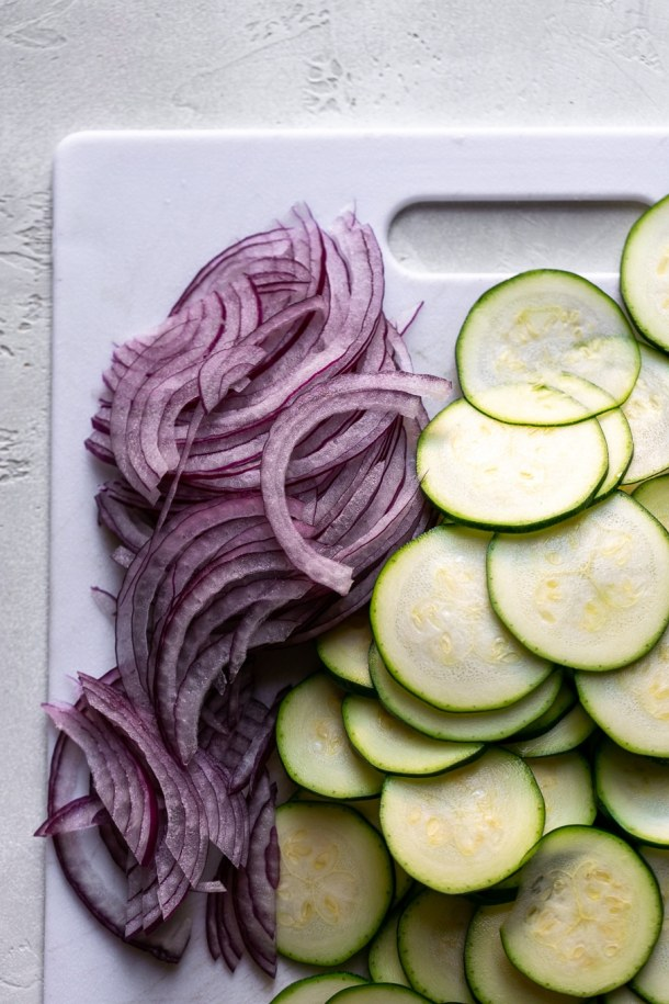 Cutting board with thinly sliced red onion and zucchini