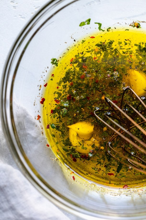 Close up shot of olive oil, garlic, herbs, and spices being whisked in a bowl