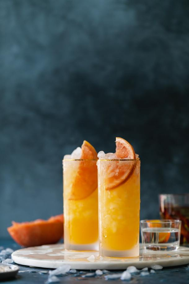 Straight on shot of grapefruit cocktails against a dark blue background