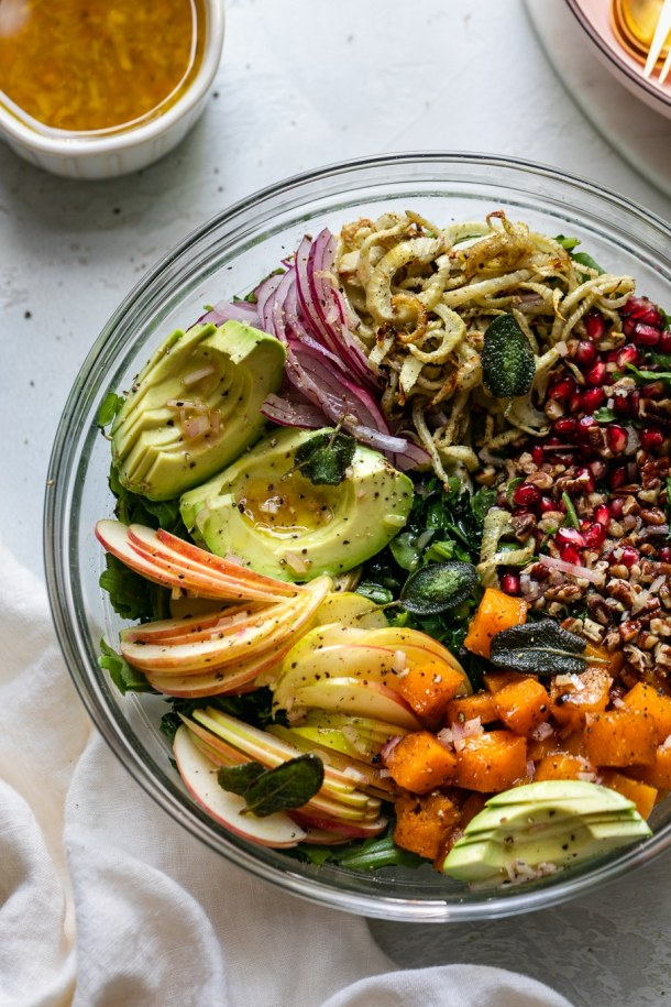 Overhead close up shot of a bowl filled with piles of colorful salad ingredients