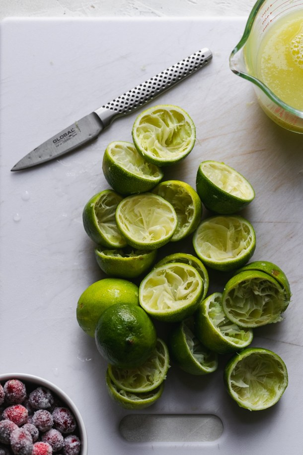 Overhead shot of juiced limes on a cutting board with a knife