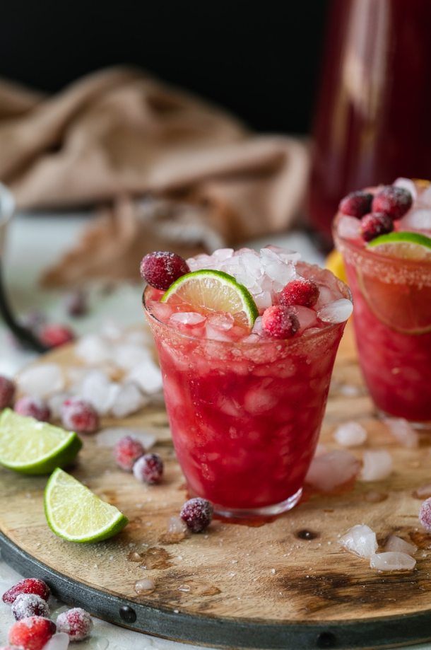 Close up shot of a cranberry margarita tarnished with lime and sugared cranberries