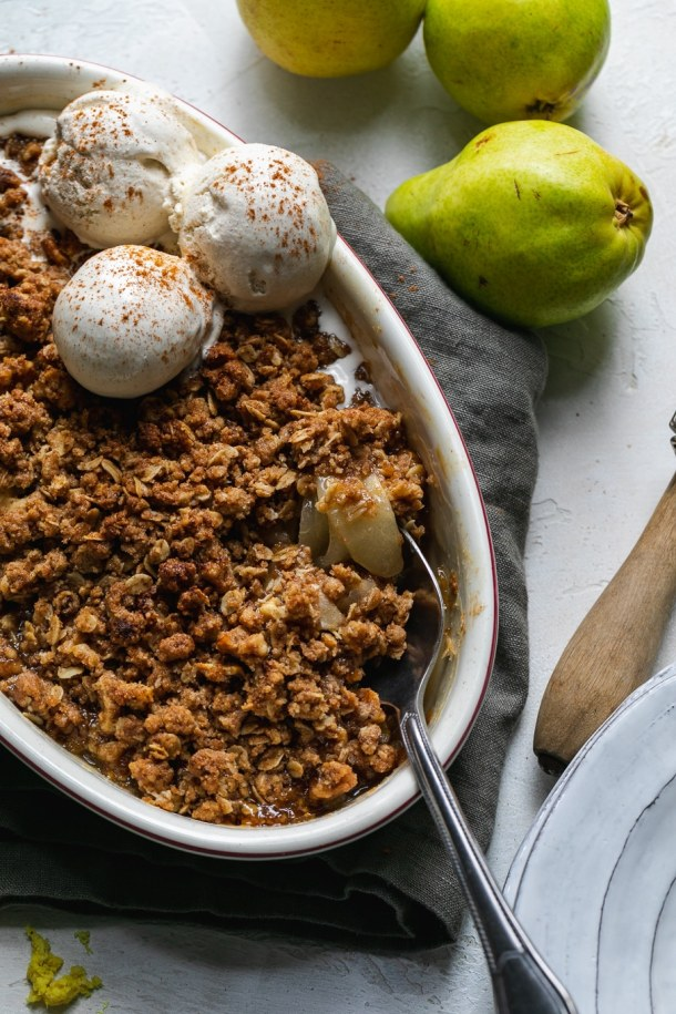 Overhead close up shot of a pear crisp with vanilla ice cream and a spoon digging in