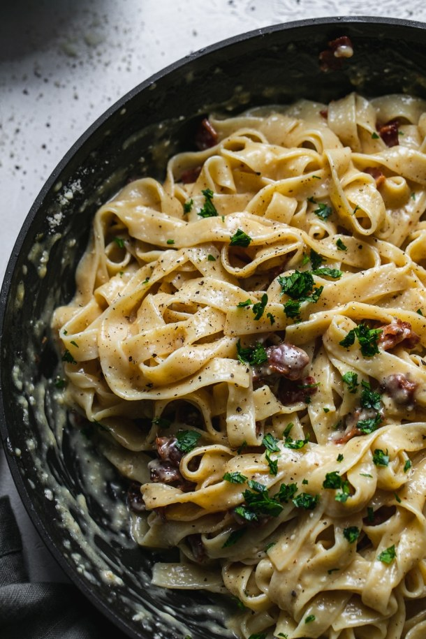 Overhead close up shot of a skillet filled with creamy carbonara pasta