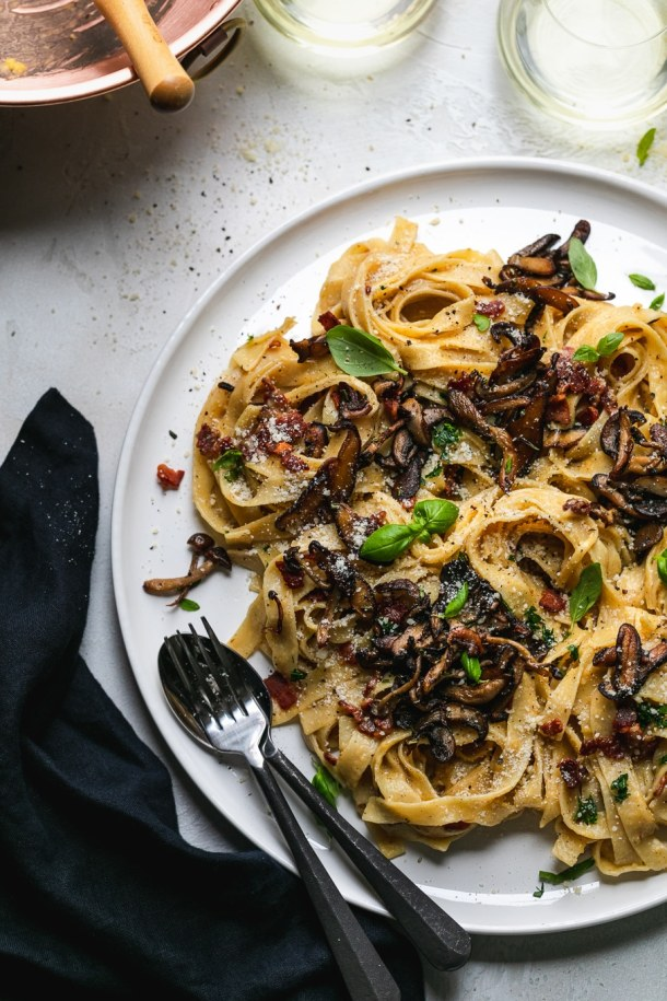 Overhead shot of pasta with mushrooms and herbs with a fork and spoon resting on the plate