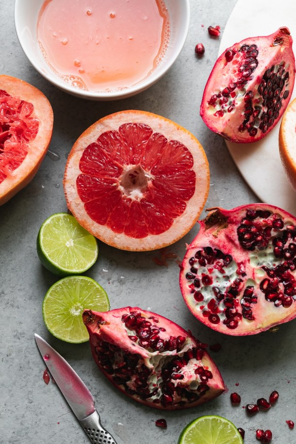 Close up shot of grapefruit, lime, and pomegranate halves