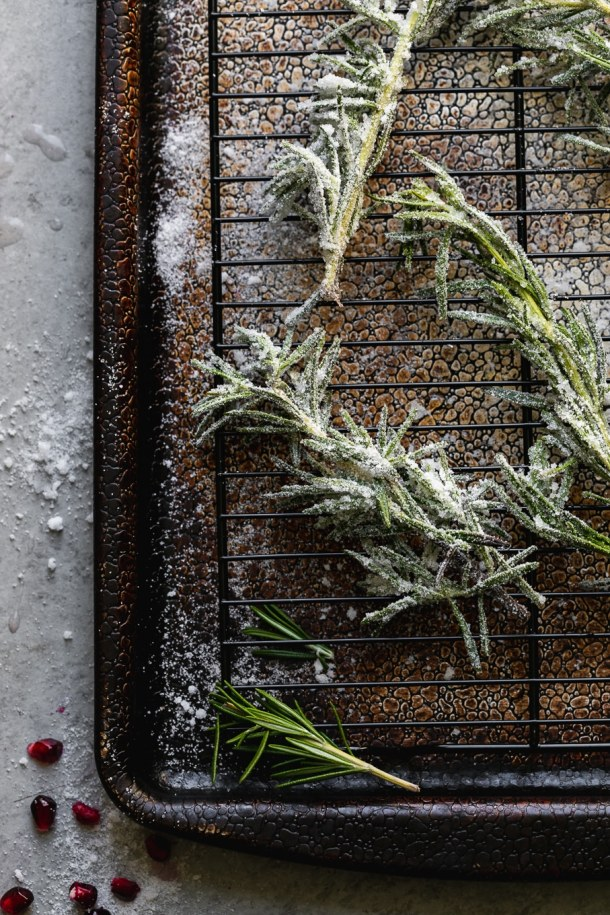 Overhead shot of sugared rosemary sprigs on a cooling rack