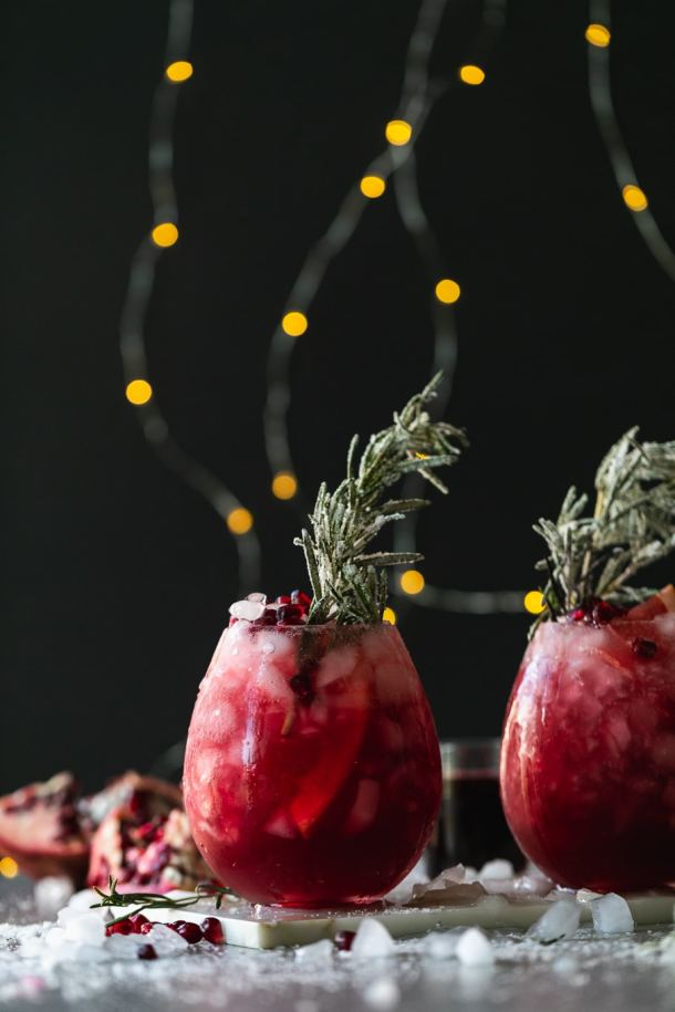 Straight on shot of deep pink cocktails against a black background with string lights
