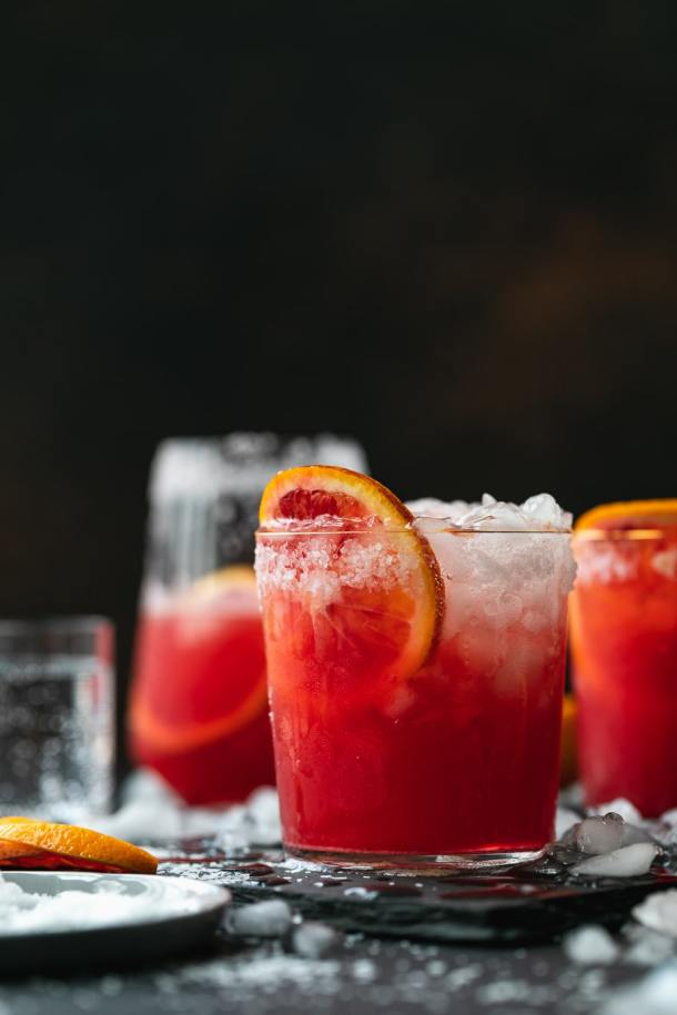 Straight on shot of a blood orange paloma against a dark background