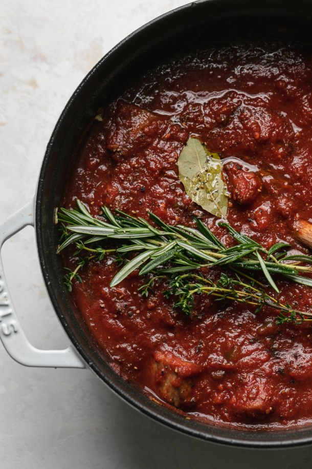 Overhead close up shot of a dutch oven filled with tomato sauce, rosemary, thyme, and bay leaves