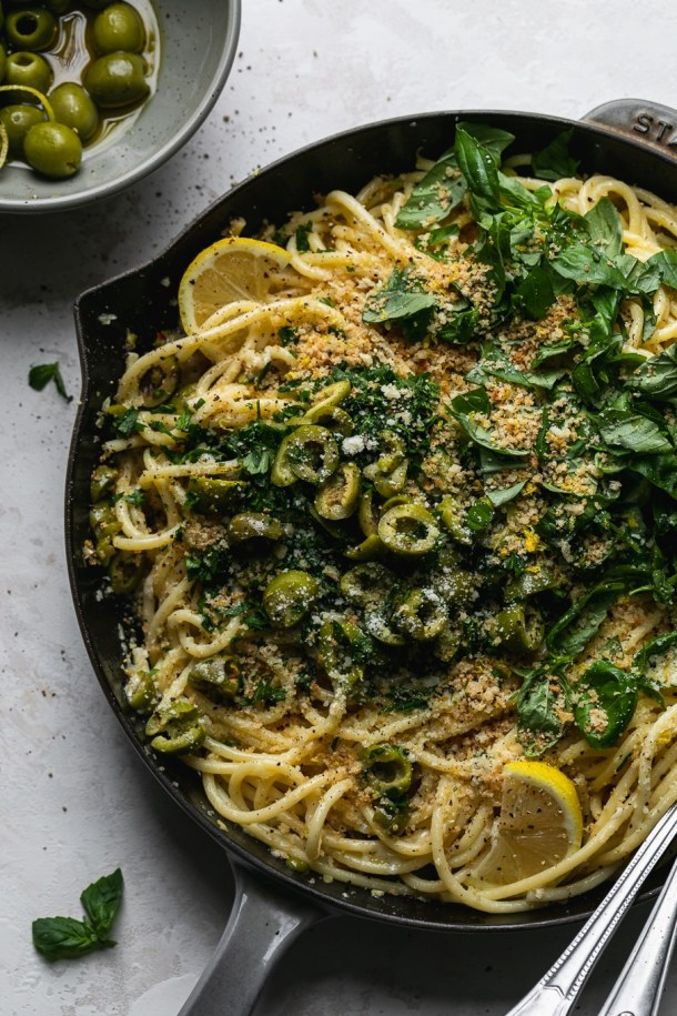 Overhead shot of olive pasta in a skillet topped with herbs
