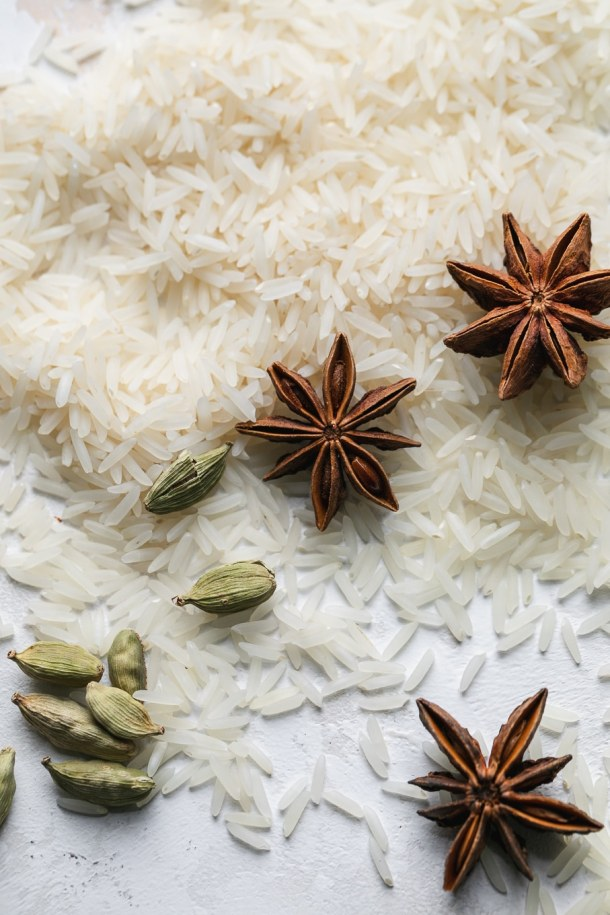 Overhead close up shot of rice, star anise, and cardamom pods
