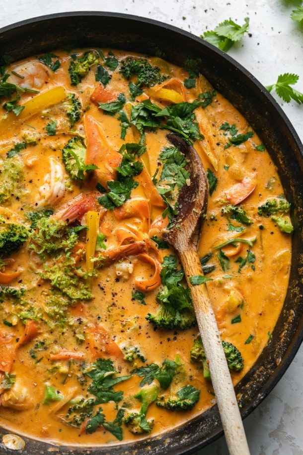 Overhead shot of a skillet filled with veggie red curry and a wooden spoon