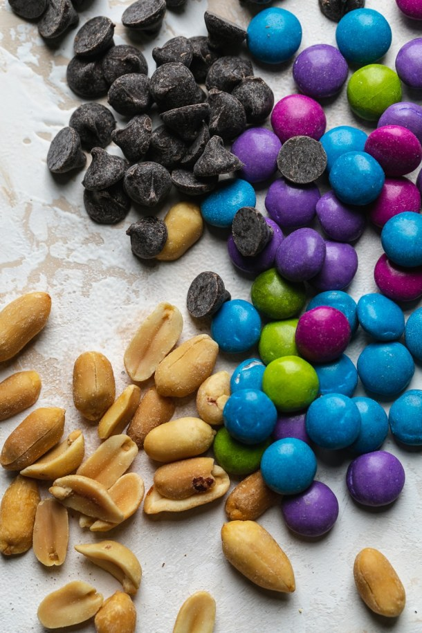 Super close up shot of peanuts, colorful candy coated chocolate pieces, and chocolate chips