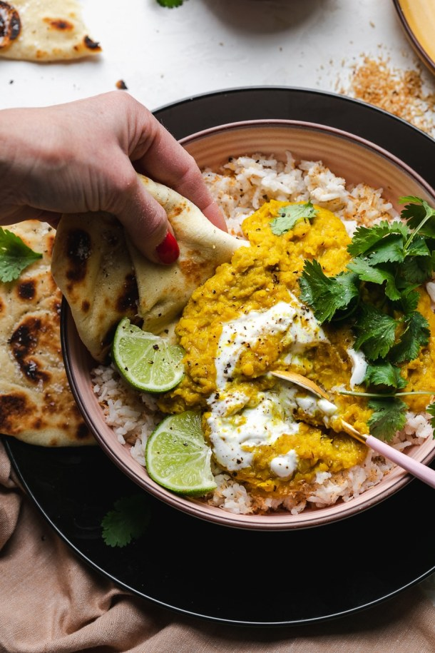 Overhead close up shot of a hand taking a scoop of lentil dal and coconut rice with naan bread