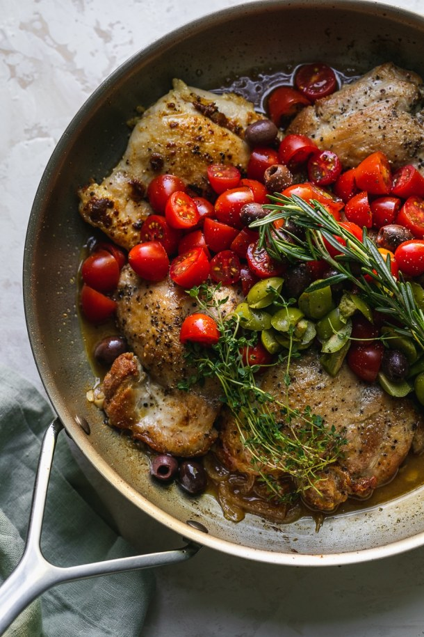 Overhead shot of a skillet with chicken thighs, tomatoes, olives, and herbs