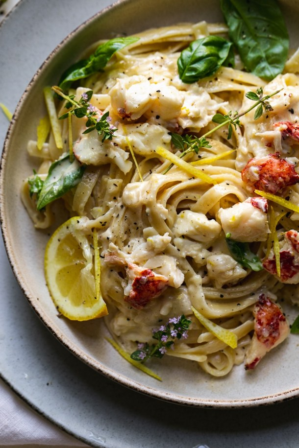 Overhead close up shot of a bowl of pasta with lemon, lobster, and herbs