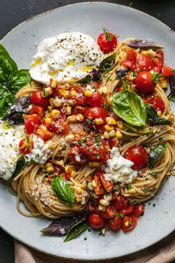 Overhead close up shot of pasta with tomatoes, basil, corn, and cheese