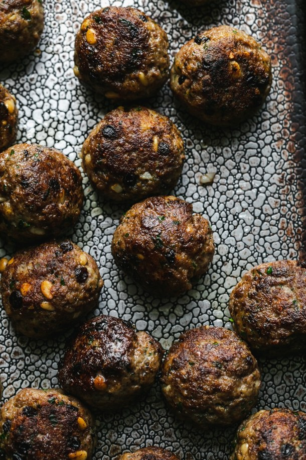 Overhead close up shot of Sicilian meatballs on a baking sheet