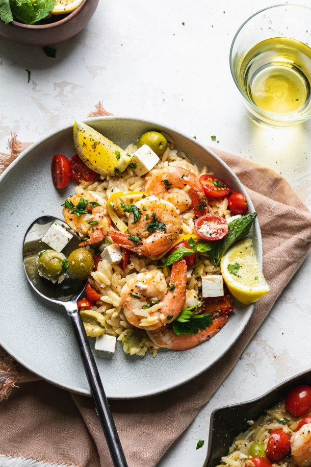 Shot of a bowl of Mediterranean shrimp orzo with a glass of white wine on the side
