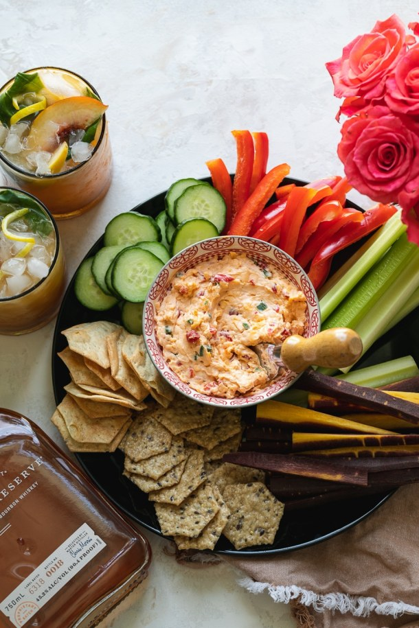 Overhead shot of 2 cocktails and a veggie platter with pimento cheese