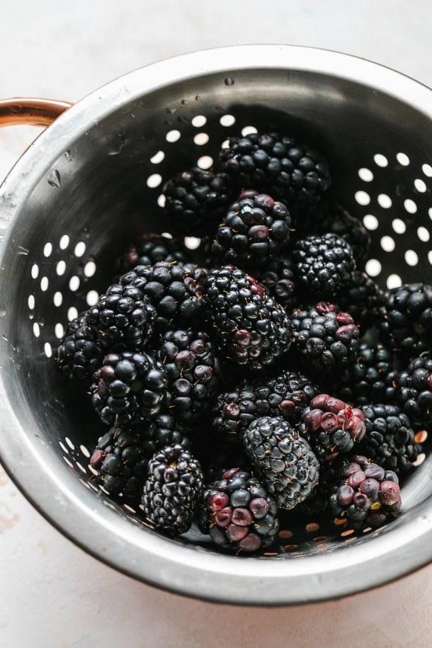Close up shot of a colander filled with blackberries