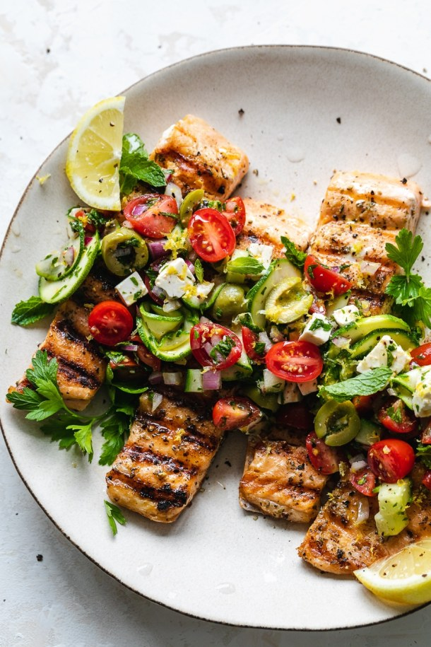 Overhead shot of grilled salmon topped with marinated zucchini greek salad