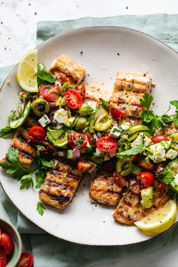 Overhead shot of grilled salmon topped with marinated greek salad