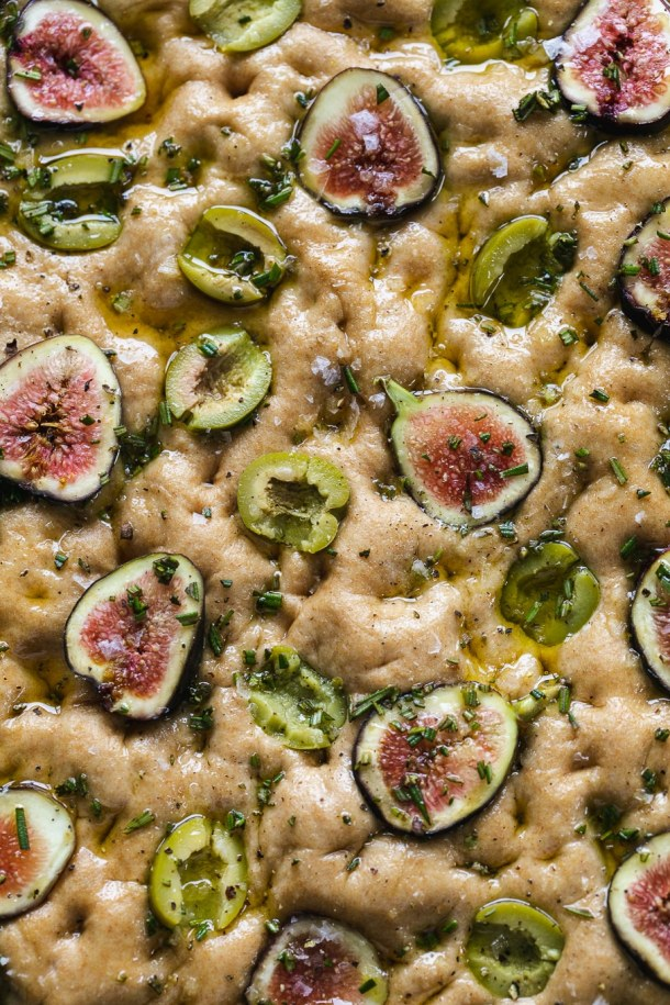 Super close up shot of focaccia dough studded with figs, olives, rosemary, and olive oil