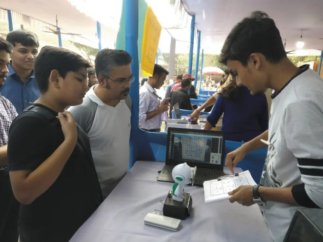 Arijit holds out a sudoku puzzle for the robot to scan and solve; at the moment, it needs to be held steady