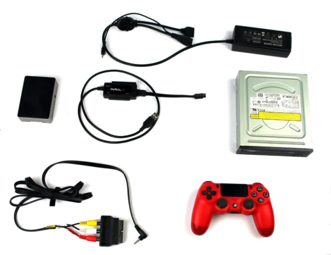 This build included an internal PC DVD-ROM drive, an externally powered SATA- to-USB adapter, a composite video out cable and SCART adapter, a heat-sink case, and controller