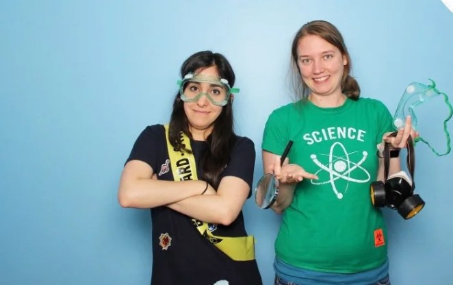 Dallas in a green t shirt stood next to Estefannie in a black t shirt on a blue background. Estefannie is wearing safety googles