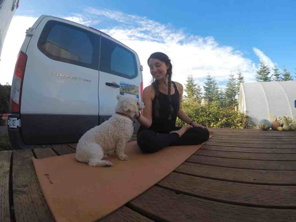 girl and dog doing yoga on wooden deck in front of van