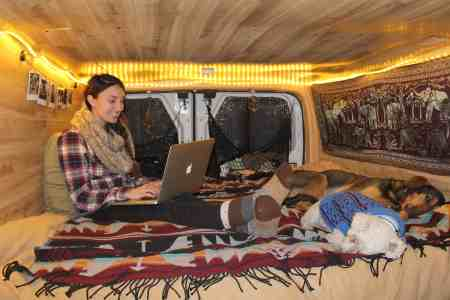 girl in van with dogs making a remote income
